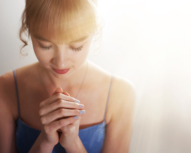 A young woman holding her hands in prayer on white background.